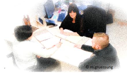 Auf dem Foto sieht man drei Personen, zwei Frauen und ein Mann die von der Kamera aus der Draufsicht fotografiert wurden. Alle drei sitzen sich an einem Schreibtisch gegenüber wobei eine Person vor, eine Person hinter und eine Person an der Seite des Schreibtisches sitzt. Auf dem Schreibtisch liegt eine Gesprächsmappe und Schreibutensilien. Die drei Personen sind in ein aktives Gespräch vertieft. Im Hintergrund ist ein Computer, ein Telefon, eine Tastatur und Schreibutensilien zu sehen. Über das Foto wurde ein Filter geschoben der dafür sorgt, dass die Personen auf dem Foto nur sehr unscharf abgebildet sind. Das Foto vermittelt eine freundliche Atmospäre.